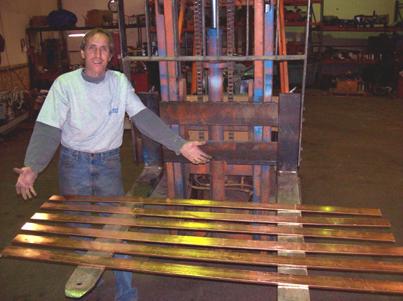 Jim Husted with the copper stock that will become hundreds of parts for the 13 module system.
